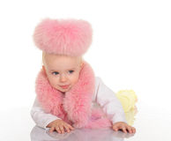 Cute baby in pink fur lying on white background Royalty Free Stock Images