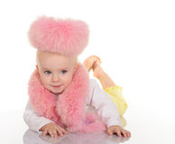 Cute baby in pink fur lying on white background Stock Photo
