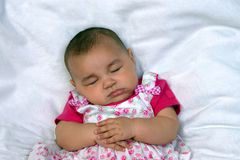 Cute baby in pink sleeping. Horizontal portrait of a baby girl asleep on a fuzzy blanket stock photos