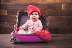 Cute baby in pink travel bag. On wooden background Stock Photo