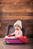 Cute baby in pink travel bag. On wooden background Royalty Free Stock Photography