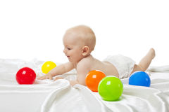 Cute baby play in bed with color balls Stock Images