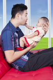 Cute baby play with father on sofa Stock Photo