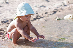 Cute baby playing on the beach. With water royalty free stock image