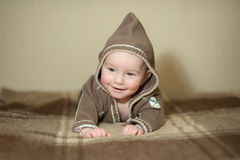 Cute baby playing on the bed, smiling and posing to camera Royalty Free Stock Image