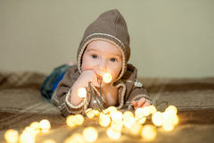Cute baby playing on the bed, smiling and posing to camera Stock Photos