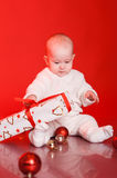 Cute baby playing with christmas presents and decorations Royalty Free Stock Photos