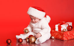 Cute baby playing with christmas presents and decorations Stock Image