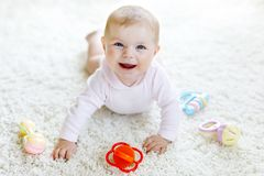 Cute baby playing with colorful pastel vintage rattle toy. New born child, little girl looking at the camera and royalty free stock images