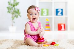 Cute baby playing with colorful toy pyramid Royalty Free Stock Images