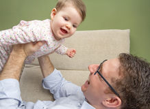 Cute baby playing with her happy father in a sofa Royalty Free Stock Photography