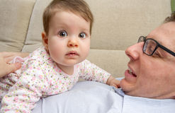 Cute baby playing with her happy father in a sofa Stock Photo