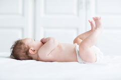 Cute baby playing with its legs and sucking on its hand Royalty Free Stock Photos