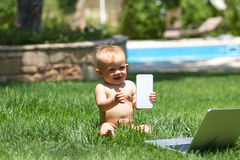 Cute baby  playing with laptop outdoors on green grass Royalty Free Stock Image