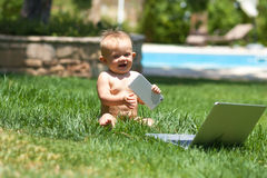 Cute baby  playing with laptop outdoors on green grass Royalty Free Stock Images