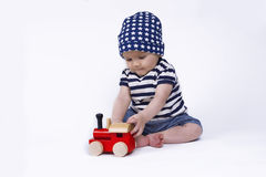 Cute baby playing with a little train. Cute baby playing with a red train Royalty Free Stock Photos
