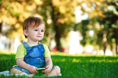 Cute baby is playing with phone on the green grass Royalty Free Stock Photography