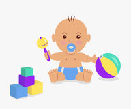 Cute baby  playing with a rattle and cubes. Royalty Free Stock Images