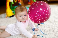 Cute baby playing with red air balloon, crawling, grabbing Royalty Free Stock Images