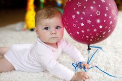 Cute baby playing with red air balloon, crawling, grabbing Stock Images