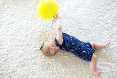 Cute baby playing with red air balloon, crawling, grabbing Stock Image