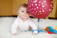 Cute baby playing with red air balloon, crawling, grabbing Stock Photography
