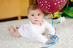 Cute baby playing with red air balloon. New born child, little girl having fun, grabbing and crawling. Family, new life. Childhood, beginning concept. Baby stock photos