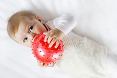 Cute baby playing with red gum ball, crawling, grabbing Stock Images