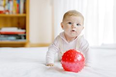 Cute baby playing with red gum ball. New born child, little girl having fun, grabbing and crawling. Family, new life. Childhood, beginning concept. Baby royalty free stock photo