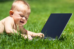 Cute baby  playing  and smiling with laptop outdoors on green grass Royalty Free Stock Image