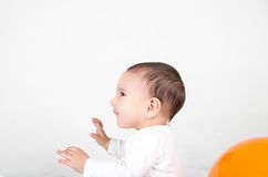 Cute baby playing surprised. With hands up in white background and ballon Stock Photos