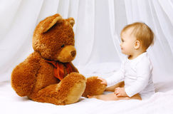 Cute baby playing with teddy bear Royalty Free Stock Images