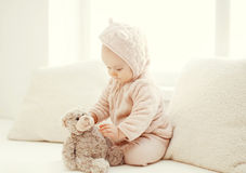 Cute baby playing with teddy bear toy home in white room Royalty Free Stock Photos