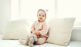 Cute baby playing with teddy toy home in white room near wind. Cute baby playing with teddy toy at home in white room near window Royalty Free Stock Photos