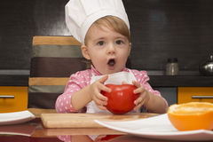 Cute baby playing with tomato in the kitchen. Royalty Free Stock Photos