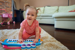 Cute baby playing with toy piano Royalty Free Stock Photos