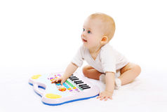 Cute baby playing with toy piano on a white Stock Photo