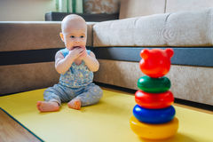 Cute baby playing with toy sitting on the floor Stock Photos