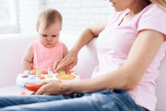 Cute baby playing toy on sofa with mother. stock photos
