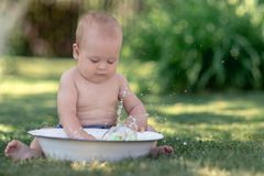 Cute baby playing with a tub of water. Cute baby hot summer day playing with a tub of water in the garden stock photo