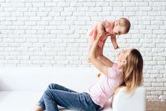 Cute baby playing with young smiling mother. royalty free stock image