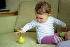 Cute baby plays with fruit Stock Images