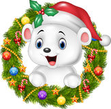 Cute baby polar bear holding Christmas Wreath with ribbons, balls and bow Royalty Free Stock Image