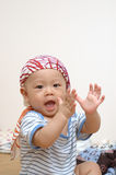 Cute baby portrait. It is a cute chinese baby, he is claping his hands Stock Photos