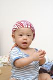 Cute baby portrait. It is a cute chinese baby, he is claping his hands Stock Images