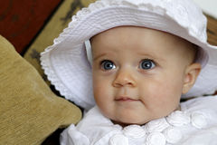 Cute baby portrait with blue eyes. Innocent infant child with blue eyes dressed in white, wearing a hat stock images