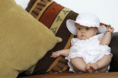 Cute baby portrait on the couch. Cute infant child with blue eyes dressed in white, wearing a hat standing on the sofa and laughing royalty free stock photo