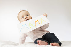 Cute baby with poster with a sign Mama. Infant boy holding greeting card for Mothers day. Stock Images