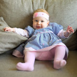Cute baby in pretty cloth sitting on couch Stock Photography