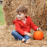 Cute baby with pumpkins on a farm Stock Photos